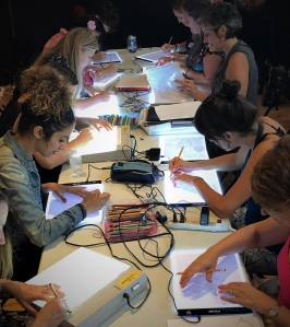 women drawing around a table using light tables